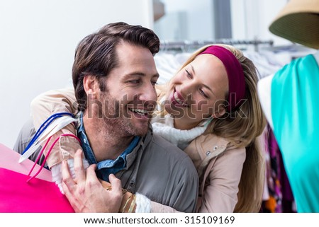 Smiling couple embracing and looking at each other in clothing store