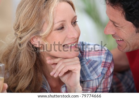 Smiling couple gazing intimately at each other with champagne glasses just in sight - stock photo