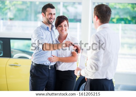 Smiling couple getting car keys from a salesman at dealership - stock photo