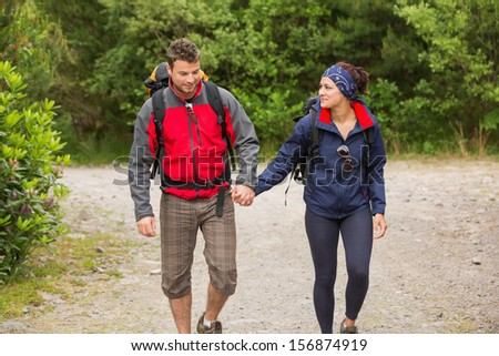 Smiling couple going on a hike together holding hands in the countryside
