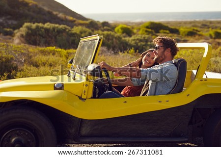 Smiling couple going on holidays together on a summer day. Young man with his girlfriend on  road trip in a open top car. - stock photo