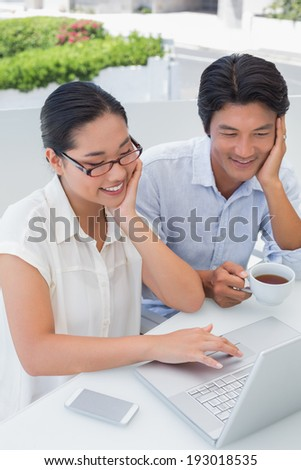 Smiling couple having breakfast together using laptop outside on a balcony - stock photo