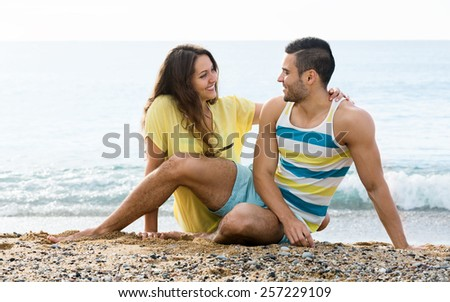 Smiling couple having romantic date on sandy beach at sunny day - stock photo