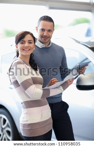 Smiling couple holding a document in a car shop - stock photo