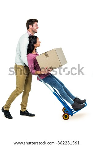 Smiling couple holding box on white screen - stock photo