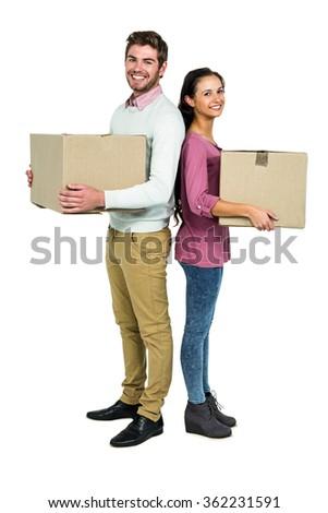 Smiling couple holding boxes on white screen - stock photo