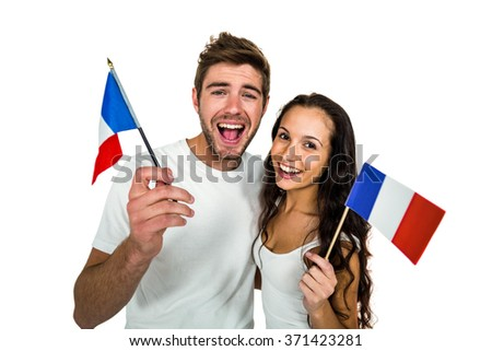 Smiling couple holding French flag on white screen - stock photo