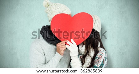 Smiling couple holding paper heart against blue background - stock photo