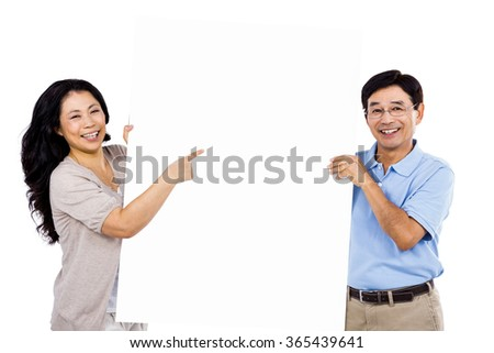 Smiling couple holding up a large sign against white background