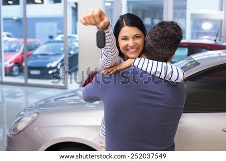 Smiling couple hugging and holding their new key at new car showroom - stock photo