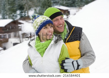 Smiling couple hugging in snow together - stock photo