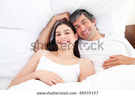 Smiling couple hugging lying in their bed at home - stock photo