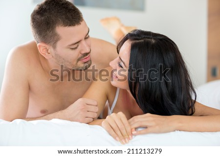 Smiling couple in bedroom in bed after sex - stock photo
