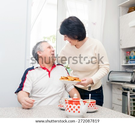 smiling couple in   kitchen drinking tea - stock photo