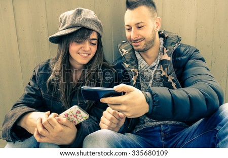 Smiling couple in love with mobile phones - Best friends having fun with smartphone - Attractive young models sharing cool sms on line -  Modern social concept of addiction to new technologies   - stock photo