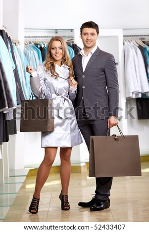 Smiling couple in shop of clothes with purchases
