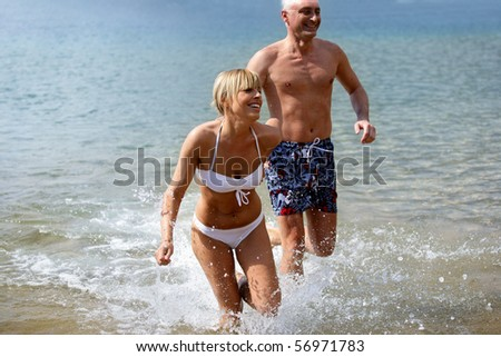 Smiling couple in swimsuit bathing in the sea