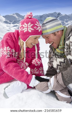 Smiling couple laying together in snow