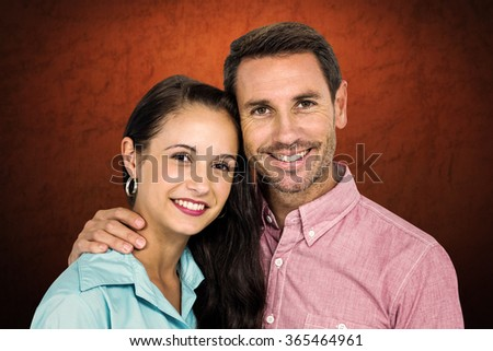 Smiling couple looking at camera against shades of brown - stock photo