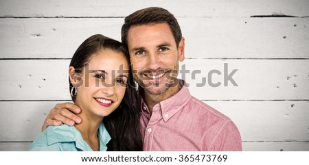 Smiling couple looking at camera against white wood - stock photo