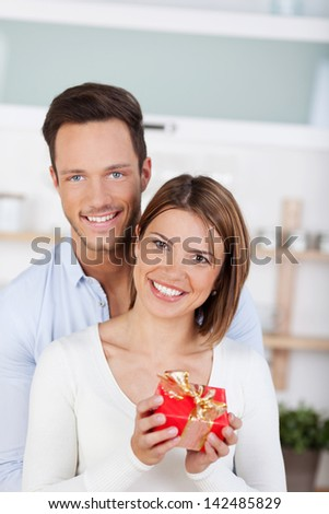 Smiling couple looking at camera. Girl with a gift box - stock photo