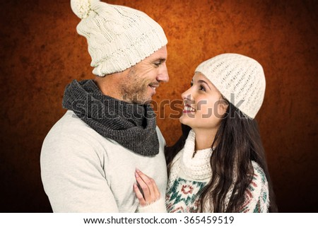 Smiling couple looking at each other against shades of brown