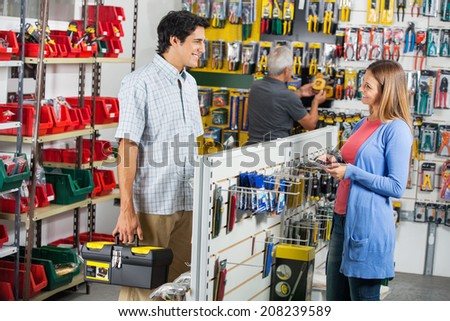 Smiling couple looking at each other while buying tools in hardware store