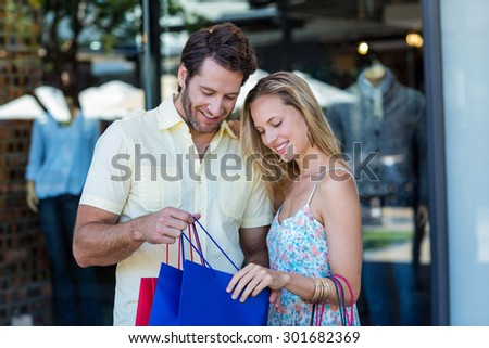 Smiling couple looking into shopping bags at shopping mall