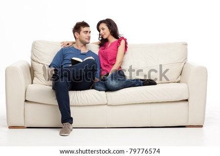 smiling couple looking romantically at each other book - stock photo
