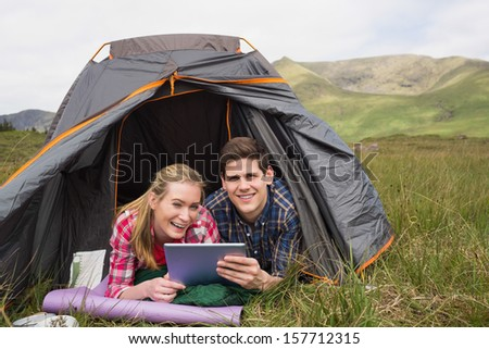 Smiling couple lying in their tent and using digital tablet looking at camera - stock photo