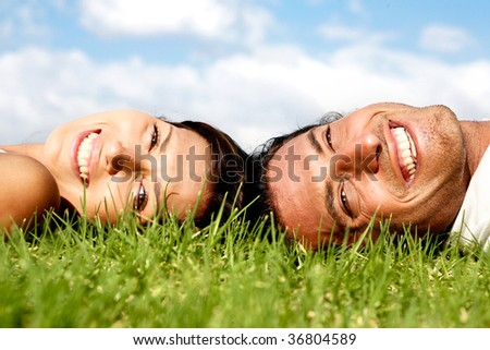 Smiling couple lying on grass and relaxing - stock photo