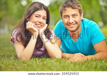 Smiling couple lying on lawn - stock photo