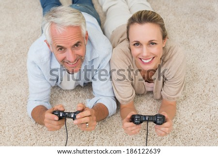 Smiling couple lying on rug playing video games at home in the living room