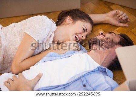 Smiling couple lying on the floor in their new home - stock photo