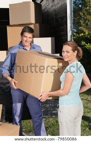 Smiling couple moving boxes at their new home - stock photo
