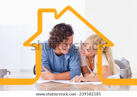 Smiling couple moving in a new house against house outline - stock photo