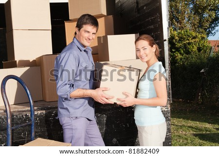 Smiling couple moving luggage at their new house - stock photo