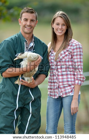 Smiling couple of duck breeders standing outdoors - stock photo