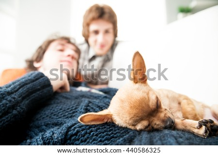 smiling couple of men that could be either gay or friends with a small cute dog