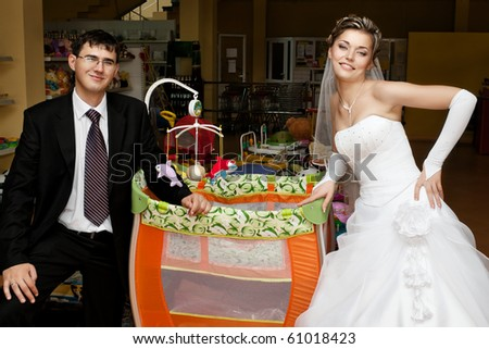 Smiling couple of newlyweds in store next to baby crib with toys