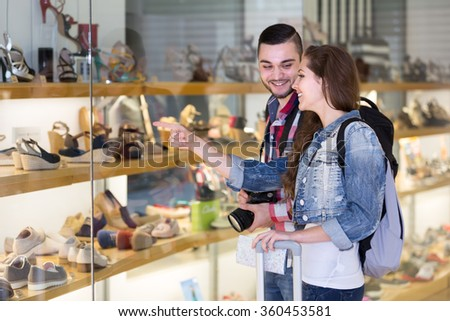 Smiling couple of tourists. Woman points at a pair of shoes she wants her boyfriend to buy for her - stock photo