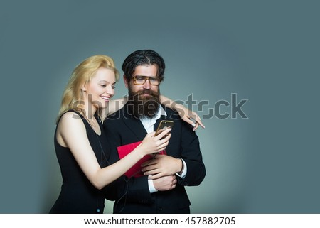 Smiling couple of young blond woman in black dress and handsome bearded hipster man in glasses suit with folder look in smartphone on grey wall