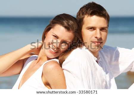 Smiling couple on a beach on a bright sunny day