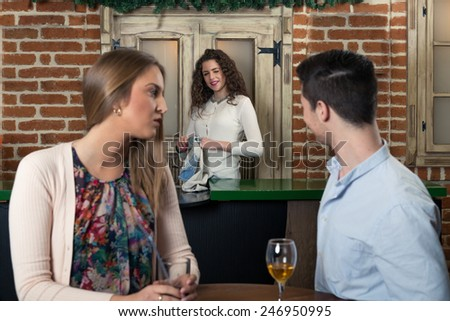 Smiling couple on a date at a bar, man flirting with a waitress... - stock photo