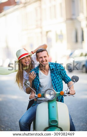 Smiling couple on a scooter outdoors - stock photo