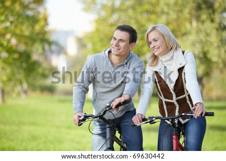 Smiling couple on bicycles in the park - stock photo