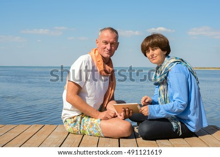 Smiling couple on the beach enjoying life and communicate with friends using tablet pc during travel.