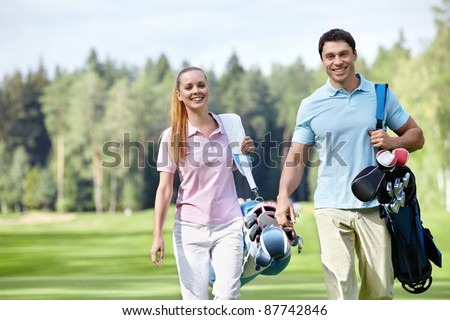 Smiling couple on the golf course - stock photo