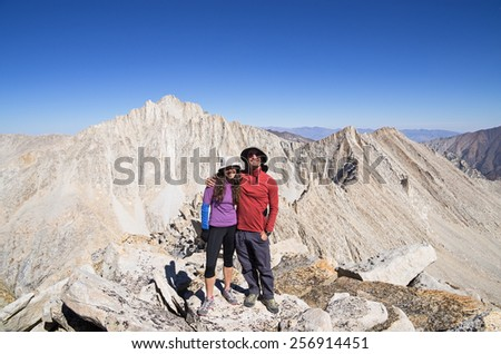 smiling couple on top of Mount Julius Caesar in the Sierra Nevada mountains - stock photo