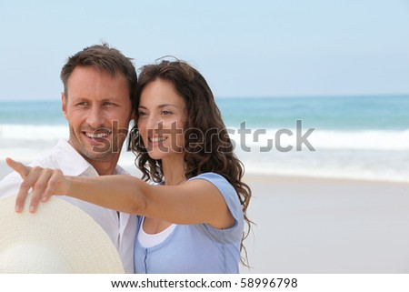 Smiling couple on vacation at the beach - stock photo